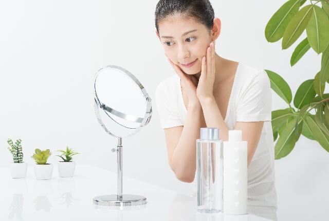鏡で化粧水を浸ける女性